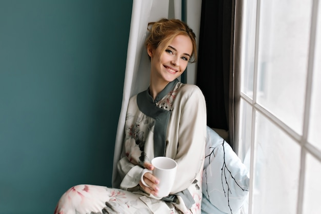 一杯のコーヒーで若い女性の笑顔、お茶を飲んだ、窓枠に座って、おはようリラックス。花にシルクのパジャマを着て、ブロンドの髪をしています。ターコイズ色の写真。 無料写真