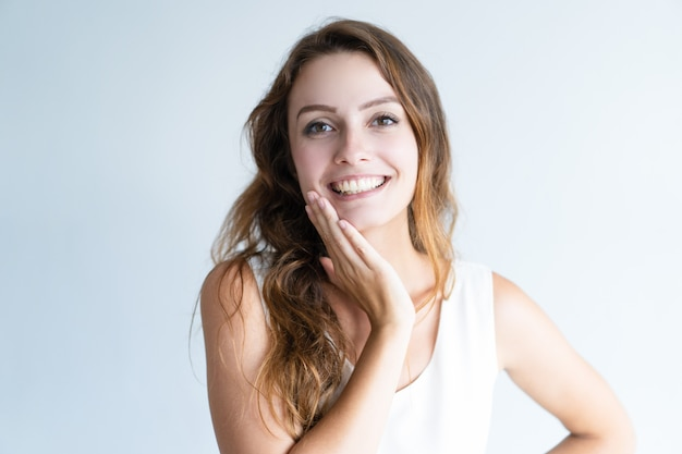 Smiling young lovely woman looking at camera and touching face Free Photo