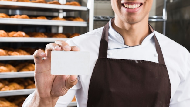Smiling young male baker holding blank white visiting card Free Photo