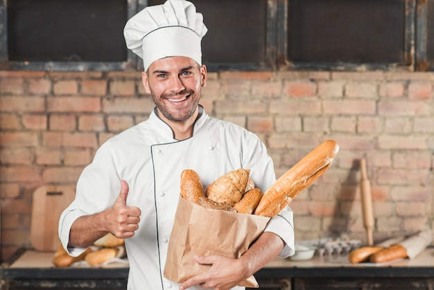 Smiling young male baker holding loaf of breads in paper bag showing thumb up sign Free Photo