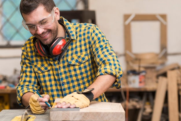 Smiling young male carpenter working with wood in his workshop Free Photo