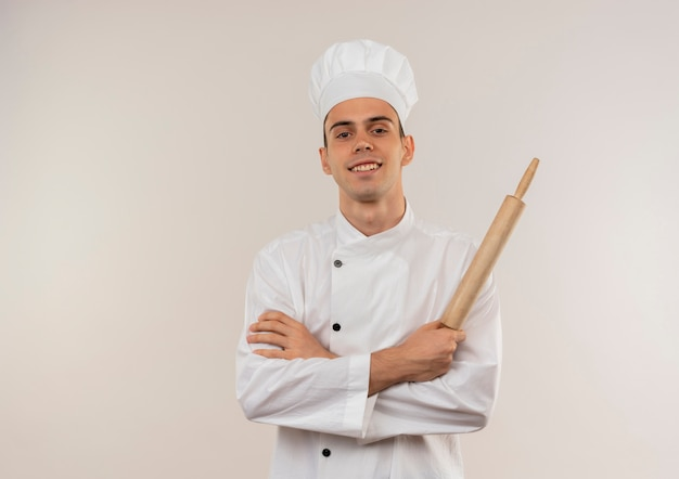 Sorridente giovane cuoco maschio indossa uniforme chef incrocio mani tenendo il mattarello con copia spazio Foto Gratuite