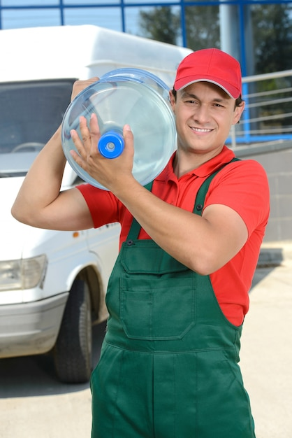Smiling young male delivery courier man with water. Premium Photo
