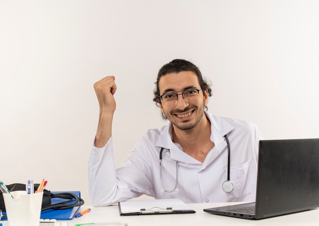 Smiling young male doctor with medical glasses wearing medical robe with stethoscope Free Photo