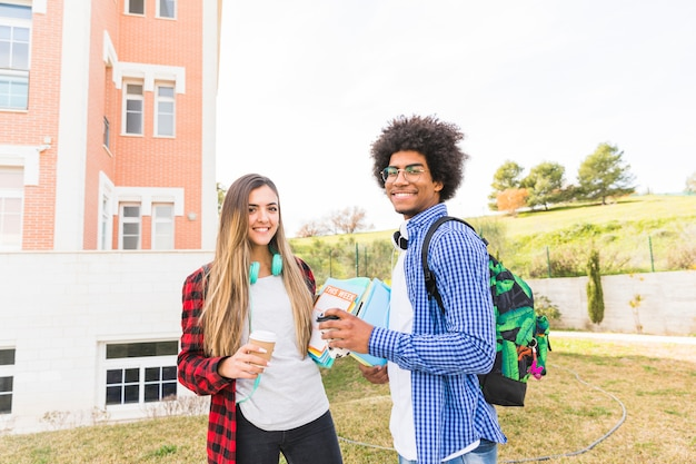 Smiling young male and female students holding takeaway coffee cup and books in hand standing at campus Free Photo