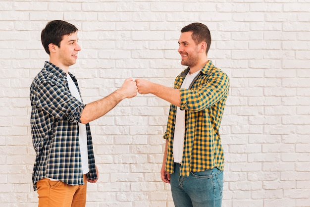 Smiling young male friends standing against white wall bumping their fist Free Photo