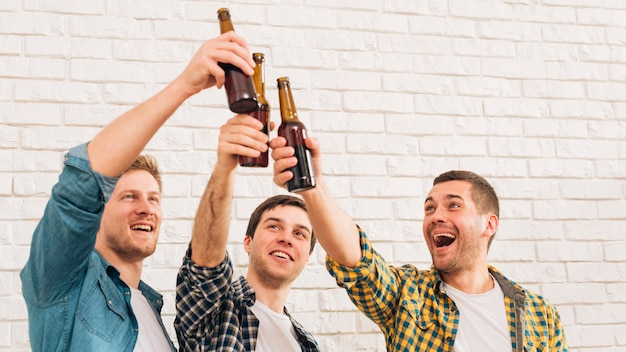 Smiling young male friends standing against white wall raising toast Free Photo