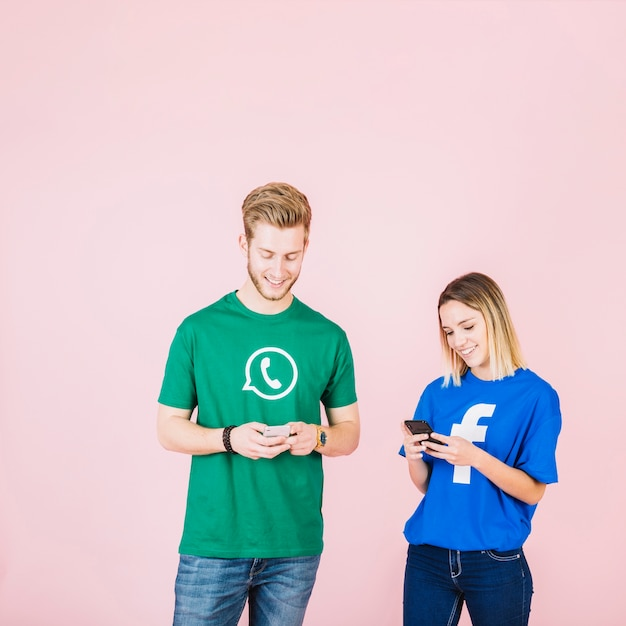Smiling young man and woman using cellphone over pink backdrop 23 2147842183
