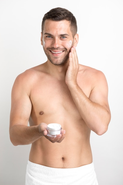 Smiling young man applying face cream looking at camera standing against white background Free Photo