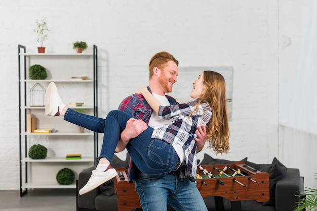 Smiling young man carrying her girlfriend in front of table soccer in the living room Free Photo