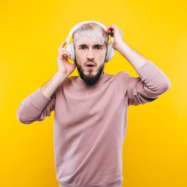 웃는 젊은 남자 캐주얼 옷을 입고 노란색 배경에 서, 한쪽을 보여주는 프리미엄 사진