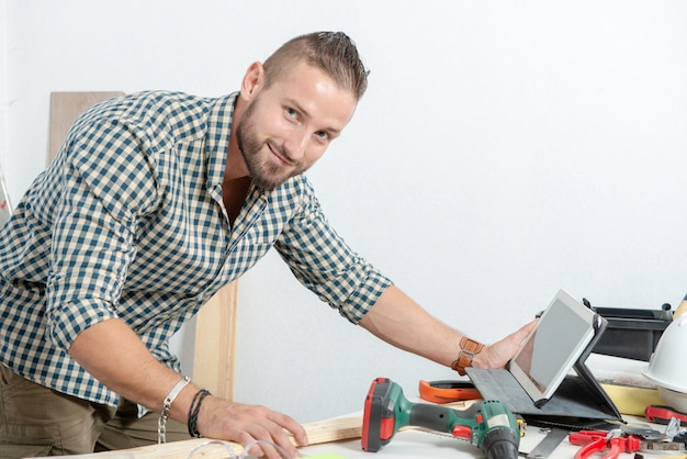Smiling young man diy at home with tablet Premium Photo