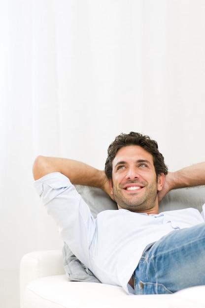 彼の未来を夢見て、自宅のソファーでリラックスした笑顔の若い男 Premium写真