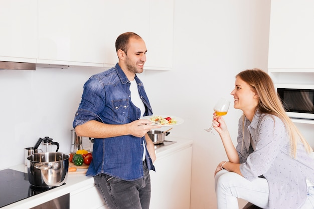Smiling young man eating salad and his wife drinking alcohol Free Photo