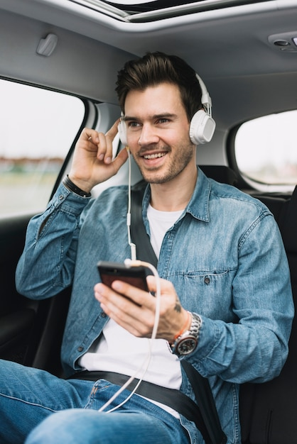 Smiling young man enjoying the music on headphone attached to cellphone Free Photo