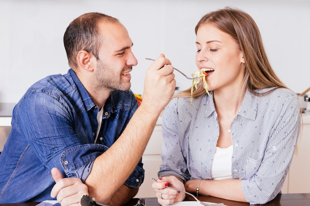 Smiling young man feeding salad to his wife with spoon Free Photo