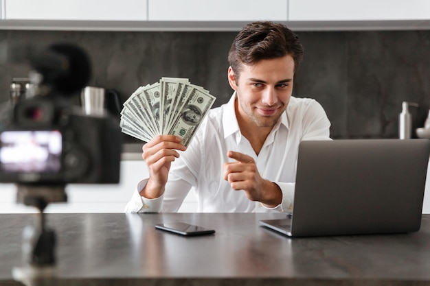 Smiling young man filming his video blog episode about new tech devices while sitting at the kitchen table with laptop and showing bunch of money banknotes Free Photo