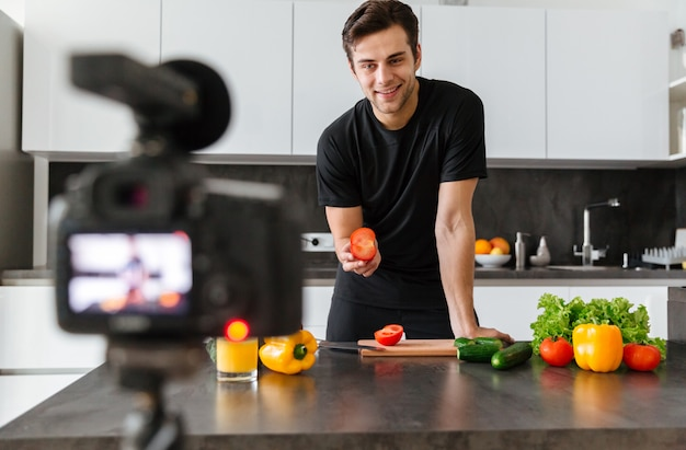 Smiling young man filming his video blog episode Free Photo
