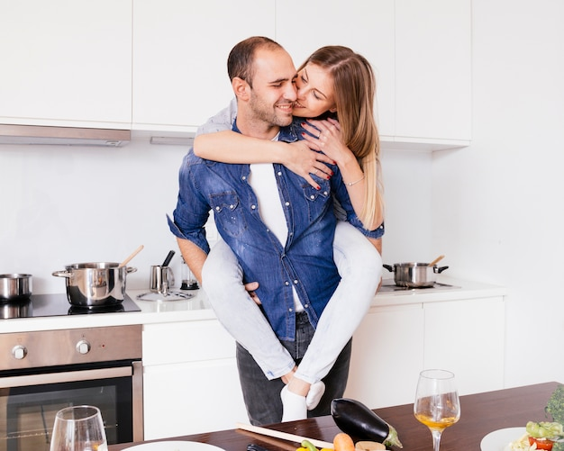 Smiling young man having fun and giving piggyback ride to his joyful wife in the kitchen Free Photo