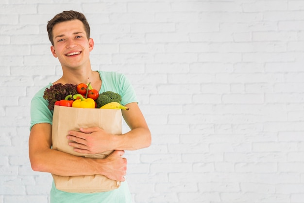 Smiling young man holding fresh vegetables and fruits in grocery paper bag Free Photo