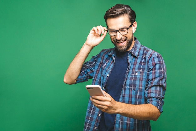 Smiling young man holding smart phone and looking at it. portrait of a happy man using mobile phone isolated over green background. Premium Photo