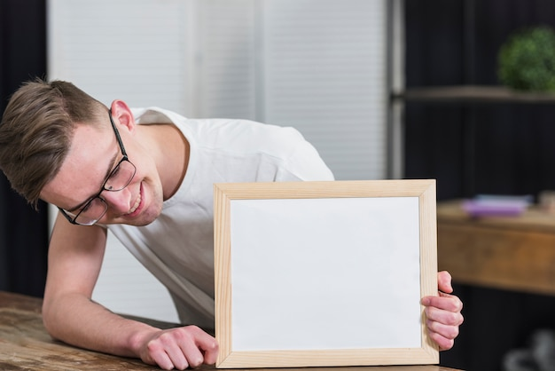 Smiling young man looking at white wooden board on table Free Photo