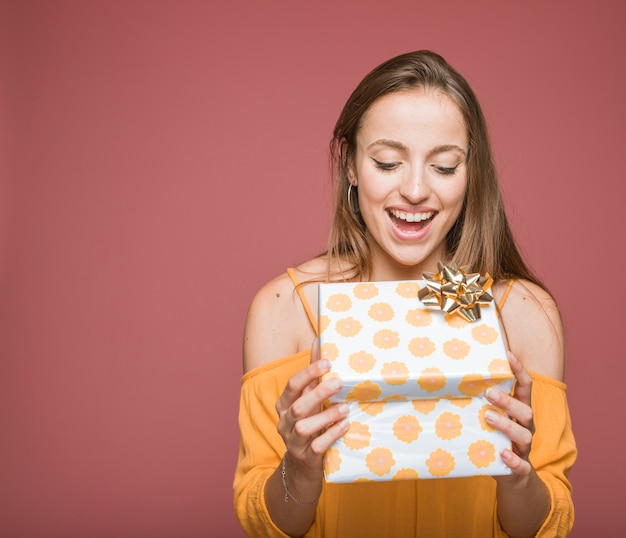 Smiling young man opening floral gift box with golden bow Free Photo