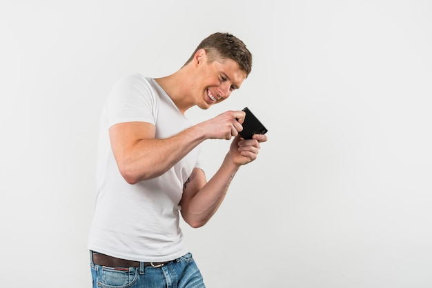 Smiling young man playing the video game on cellphone Free Photo
