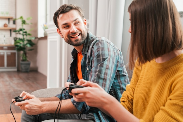 Smiling young man playing the video game with her wife Free Photo