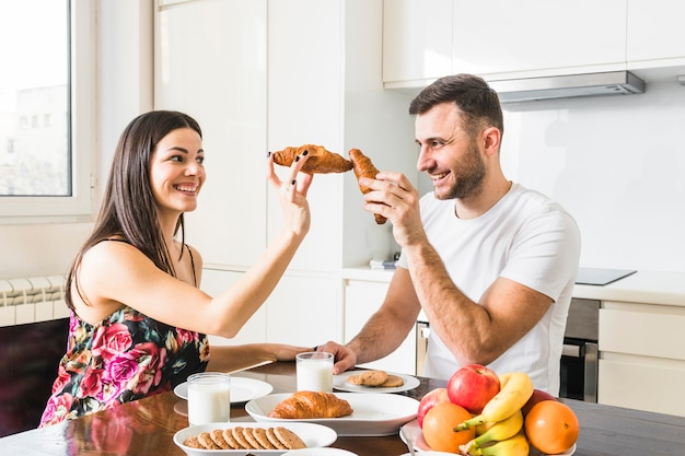 Smiling young man playing with croissant in the kitchen Free Photo