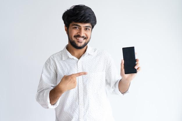 Smiling young man pointing at smartphone and looking at camera Free Photo