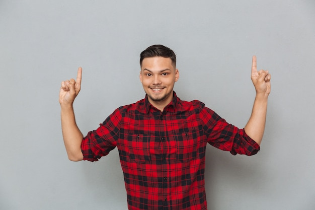 Smiling young man pointing. Free Photo