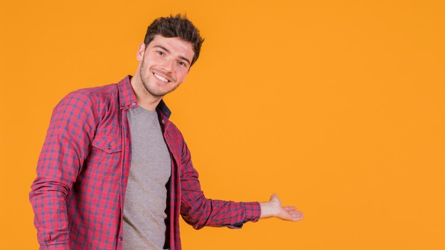 Smiling young man presenting something on an orange background Free Photo