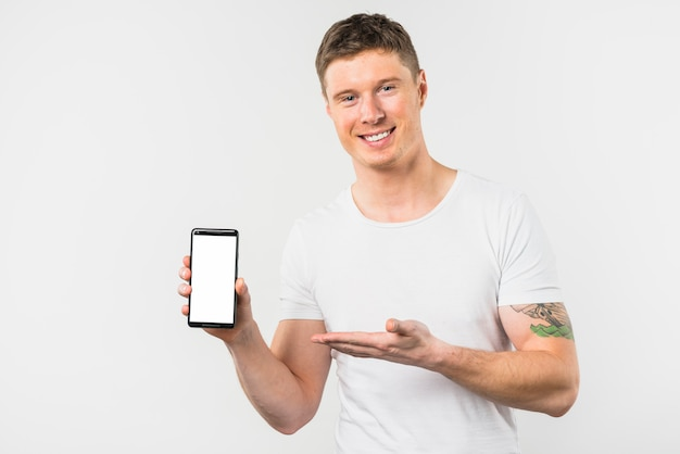 Smiling young man presenting this new smart phone with white display screen Free Photo