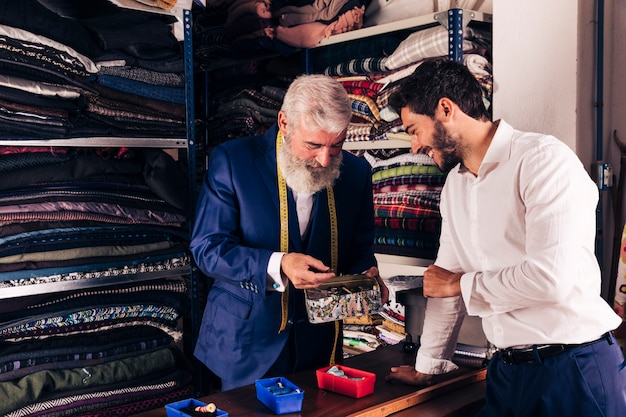 Smiling young man and senior tailor selecting button from the container in clothing store Free Photo