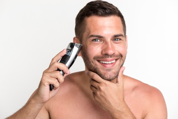 Smiling young man shaving beard with electric shaver over white background Free Photo