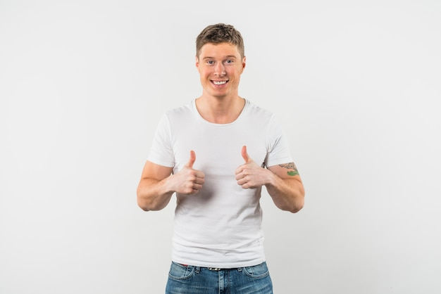 Smiling young man showing thumb up with two hands against white background Free Photo