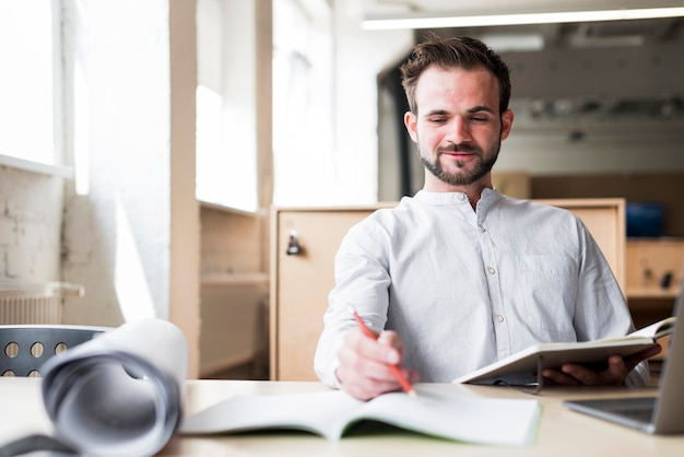 Smiling young man sitting on chair working in office Free Photo