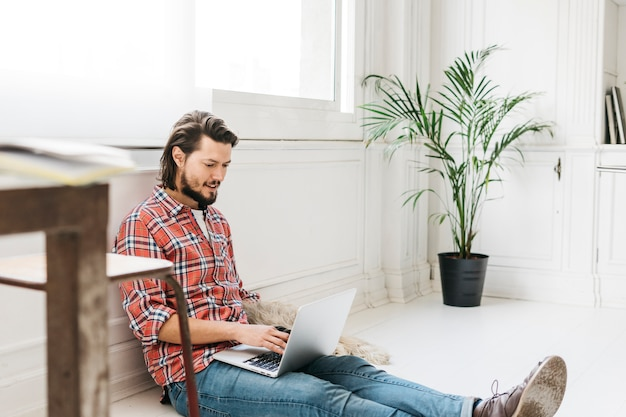 Smiling young man sitting at home using laptop Free Photo