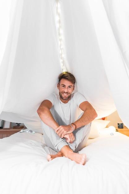 Улыбающийся молодой человек, сидя на кровати под белый занавес Бесплатные Фотографии