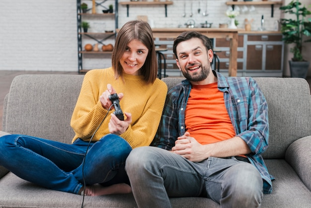Smiling young man sitting with her wife playing video game Free Photo
