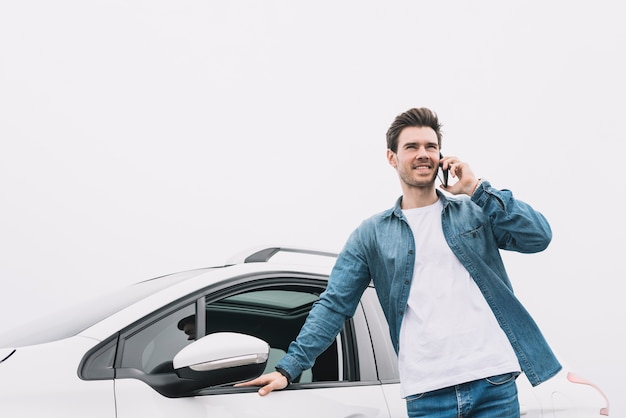 Smiling young man standing in front of car talking on smartphone Free Photo
