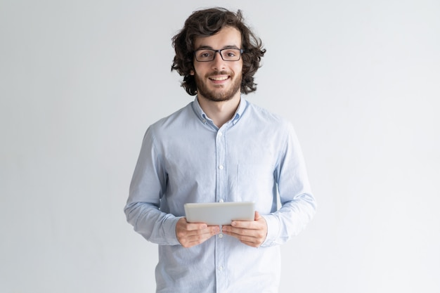 Smiling young man standing and holding tablet computer Free Photo