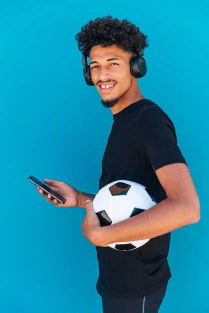 Smiling young man standing with football and phone Free Photo