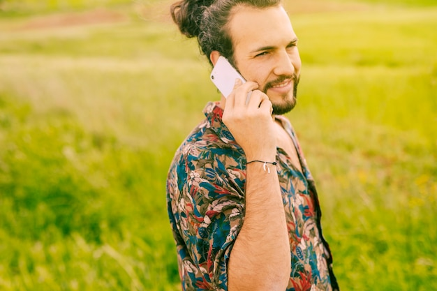 Smiling young man talking on mobile phone in field Free Photo
