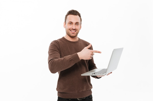 Smiling young man using laptop computer pointing. Free Photo