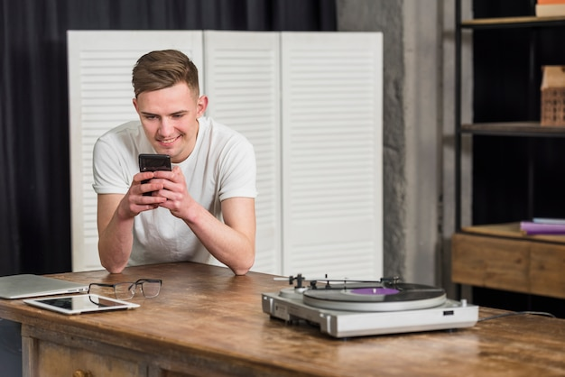 Smiling young man using mobile phone with digital tablet; eyeglasses and turntable vinyl record player on the table Free Photo