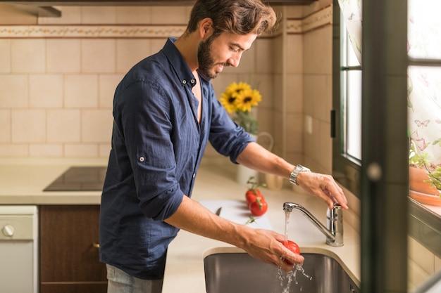Smiling young man washing tomato in sink Free Photo
