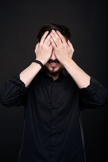 Улыбающийся молодой человек с бородой закрывает глаза руками в ожидании удивления на черном фоне Premium Фотографии