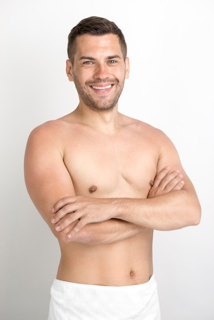 Smiling young man with crossed arm looking at camera Free Photo